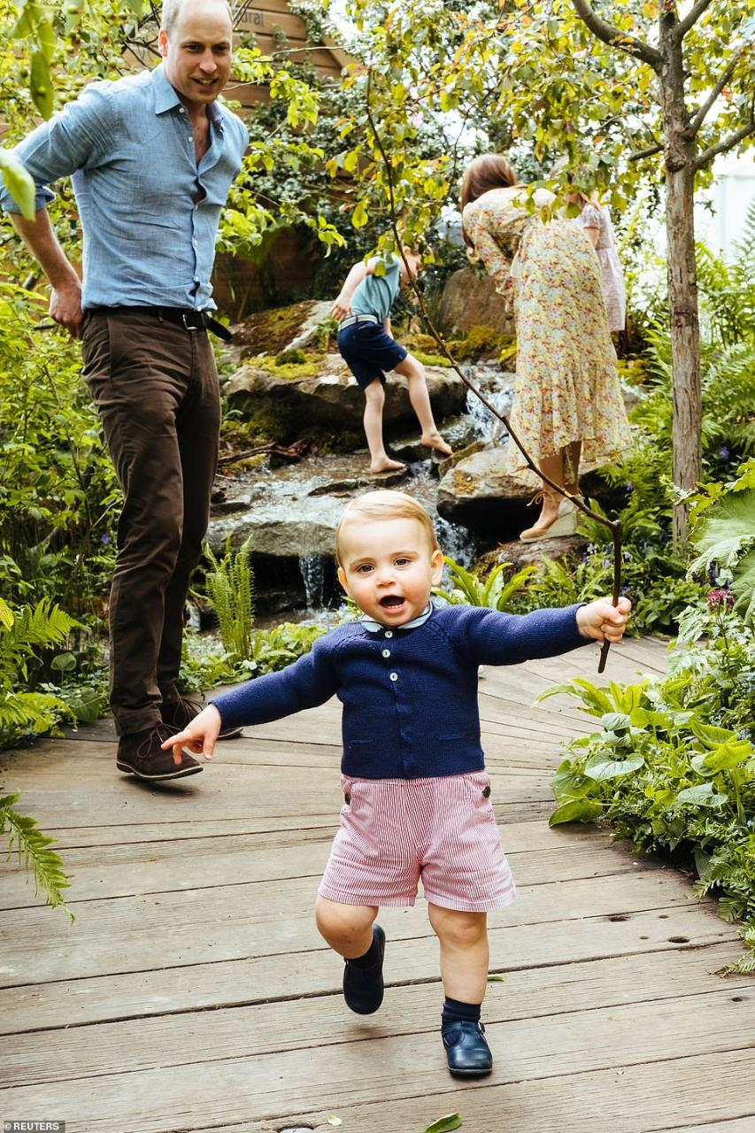 Prince William looks on as his young son Prince Louis explores an exhibit at the Chelsea Flower show with his siblings and mother on May 19, 2019